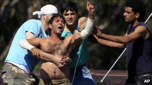 Fellow detainees grab onto a man and removed a wire he had around his neck after he threatened to jump from a rooftop at the Villawood Detention Center in Sydney (April 2011)