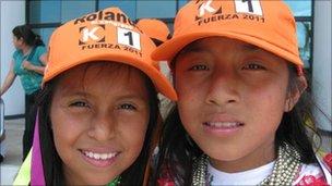 Indigenous Kichwa girls wearing trademark orange baseball caps of Keiko Fujimori's party