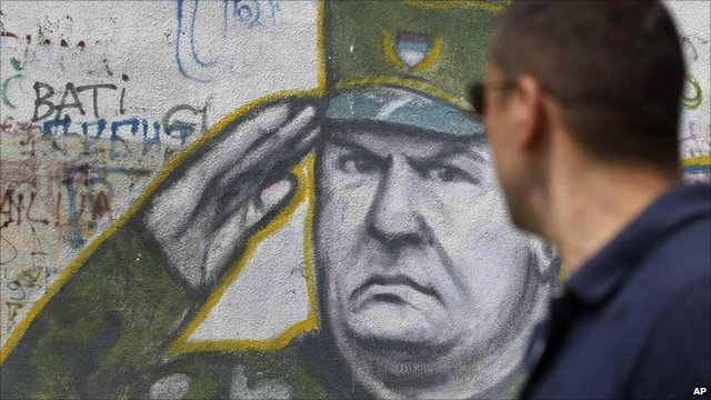 Man looks at a mural of Ratko Mladic