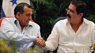 Honduran President Porfirio Lobo (left) and former president Manuel Zelaya (right) shake hands in Managua on 22 May 2011