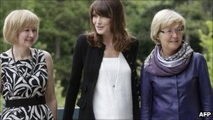 French President Nicolas Sarkozy's wife, Carla Bruni-Sarkozy (C) poses with Laureen Harper (L), wife of Canadian Prime Minister Stephen Harper and Geertrui Van Rompuy-Windels, wife of European Council President Herman Van Rompuy, on the sidelines of the G8 summit in Deauville, on Thursday