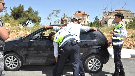 Palestinian police officers make a fake arrest as part of a training exercise in Ramallah