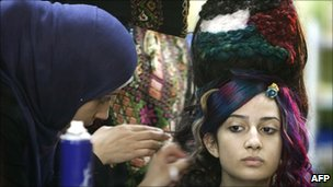 A Palestinian hairstylist works on a hair style inspired by the Palestinian political reconciliation between Hamas and Fatah on 12 May 2011 in Gaza City