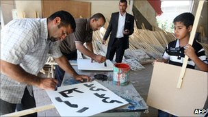Iraqi men write slogan for a demonstration in the mainly Shia suburb of Sadr City