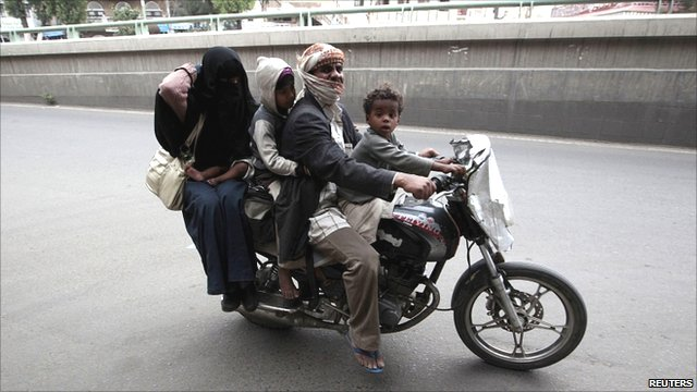 A Yemeni family on motorcycle flees their home