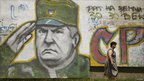 A woman walks past graffiti of Bosnian Serb fugitive General Ratko Mladic in Belgrade, 2009