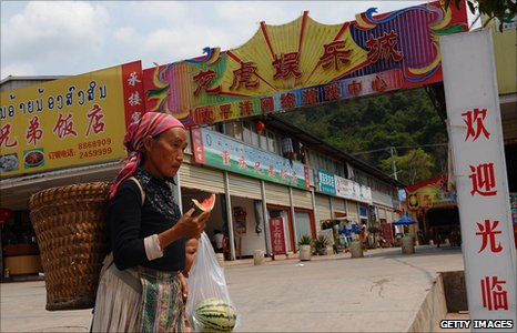 Local tribes woman walking past Chinese shops, Boten, Laos