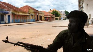 Soldier patrols a residential street in Guinea-Bissau following 2003's coup