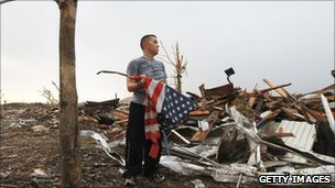 A man prepares to fold an American flag in the devastated city of Joplin, Missouri. Photo: 27 May 2011