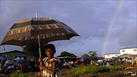 A girl stands under an umbrella with a rainbow behind her in Monrovia, Liberia - (Archive photo: 2003)