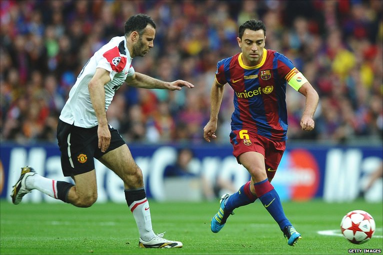 Xavi takes the ball past Giggs