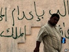 A Bahraini man walks past a mosque spray painted with pro-government graffiti