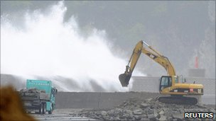 An excavator is seen as waves hit a temporary breakwater at a port that was devastated by the 11 March quake and tsunami in Miyako, Iwate prefecture