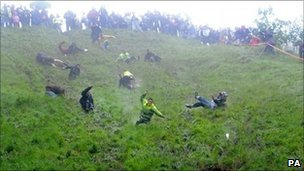 Competitors take part in the unofficial cheese rolling event on Coppers Hill