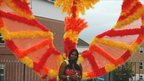 A carnival-goer wears red and yellow angel wings at the Reading Community Carnival 2011