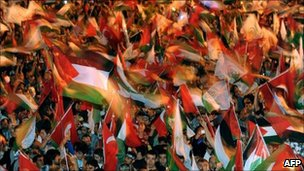 People wave Turkish and Palestinian flags during a rally in Istanbul, 20 May