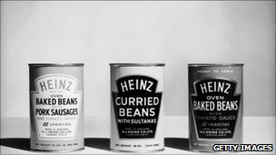 Three classic tins of Heinz beans in a black and white photograph