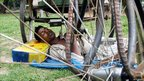 Rickshaw driver sleeps under his vehicle