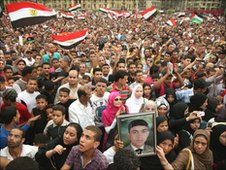 Egyptian protesters wave their national flag as they crowd Cairo's landmark Tahrir Square on May 27, 2011