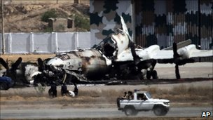 Pakistani troops drive past a destroyed navy warplane at the Mehran base in Karachi (23 May 2011)