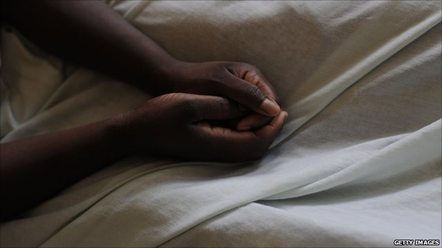 Rape victim rests her hands on her bed sheets