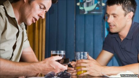 Man using smartphone in pub