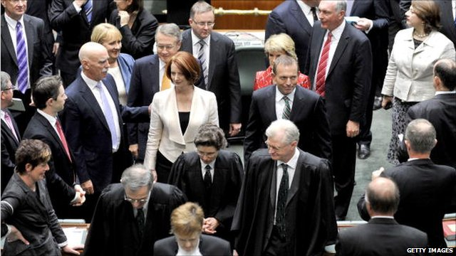 MPs file out of the Australian House of Representatives in Canberra at the official opening of parliament, 28 September 2010