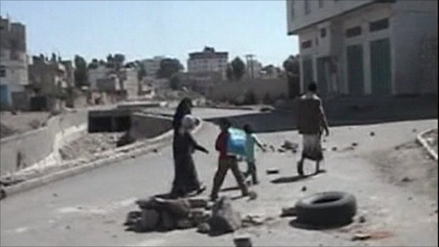 Family walk past rubble in Sanaa