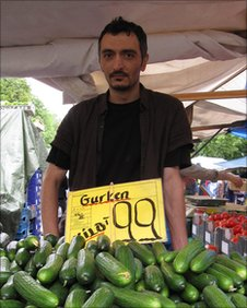 Market trader selling cucumbers in Turkish market in Berlin
