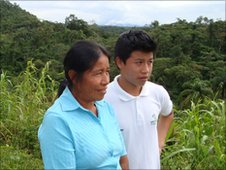 Henry and his mother stand in front of a hillside covered in fields and trees