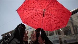 Women holding an umbrella attends an anti-government in Sanaa, 30 May 2011