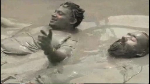 Men lying in mud