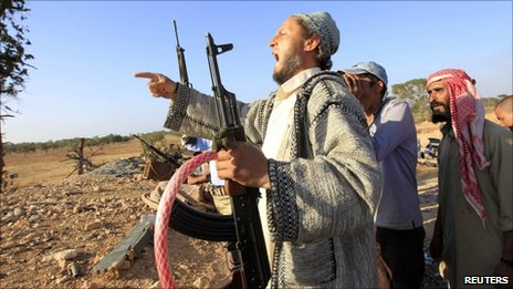 A Libyan rebel fighter shouts as his comrades drive towards the positions of Gaddafi forces at Misrata's western front line, some 25 kilometres from the city centre May 30, 2011.
