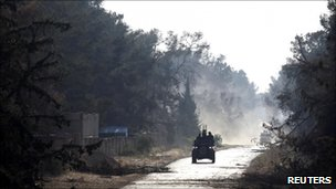 """Libyan rebel fighters drive in pickup trucks towards the positions of Gaddafi forces at Misrata""""s western front line, some 25 kilometres from the city centre May 30, 2011"""