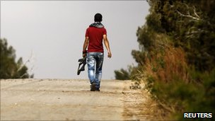 A Libyan rebel fighter walks during a reconnaissance patrol near Zlitan after Dafniyah's western front line, some 35 kilometres (22 miles) from Misrata, 24 May 2011.