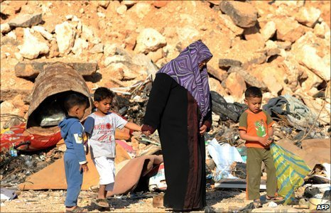 A Libyan woman walks through garbage and construction material along with her children in the Benghazi's downtown
