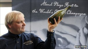 Christian Ekstrom, the diver who found the champagne, is pictured with one of the bottles. Photo: April 2011