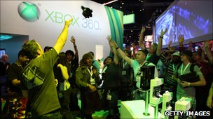Individuals waving their hands inside the Xbox booth at the 2010 E3 Expo