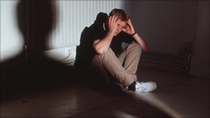 Man cowering in the corner of a dark room