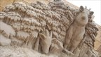 Sand sculpture of animals peeking through undergrowth in Weston-super-Mare