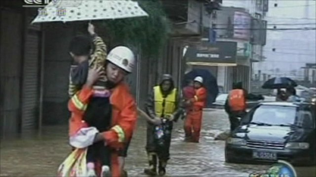 Rescue worker carries a child to safety