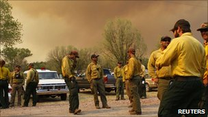 Firefighters wait to receive orders while they take a break from the Wallow Wildfire as smoke fills the sky in Luna, New Mexico on Monday