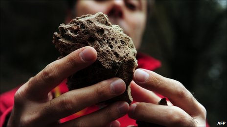 Man shows a volcanic stone from Chile's Puyehue volcano at Cardinal Samore Pass on the border between Chile and Argentina, near Osorno in southern Chile, on 6 June, 2011
