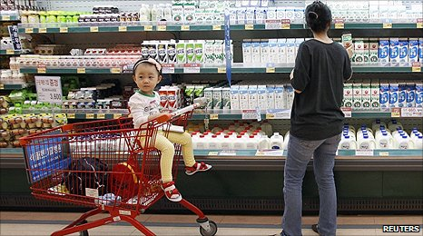 A customer looks at shelves beside a girl in a shopping trolley