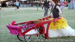 A pregnant hippy wheels her barrow at the Sunrise Celebration