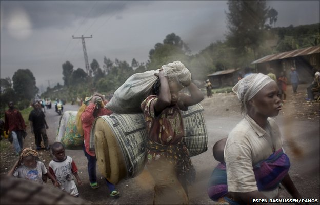 Men, women and children flee along the main road into Goma