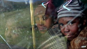 Young Lesothan shepards look out a window in a small village in Lesotho. Many of them were forced by poverty to leave school at a young age