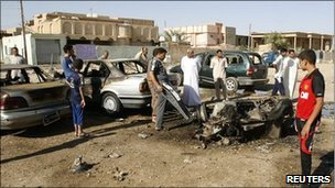 Residents gather around the remains of a vehicle used in a bomb attack, a day after blasts occurred in the Iraqi city of Ramadi (archive shot)