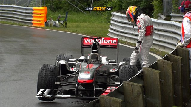 Lewis Hamilton looks at his McLaren after colliding with Jenson Button