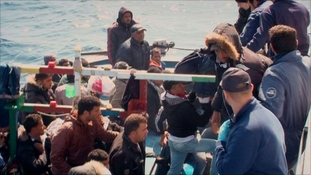 Tunisian migrants board a coast guard boat